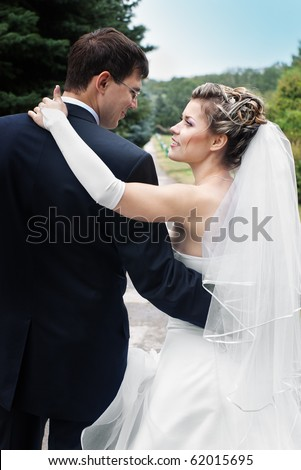 Bride and groom hugging and looking at each other outdoors in park