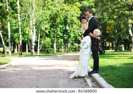 Bride and groom hugging each other gently during a walk in the summer park