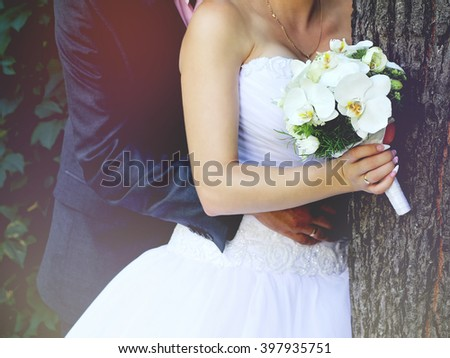 Bride and groom hugs near the tree with wedding bouquet after wedding ceremony in the green garden. Concept of family life tenderness and happiness.