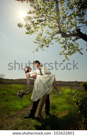 bride and groom in a field near a flowering tree - stock photo