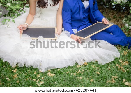 Bride and groom in a park showing empty board  for use  illustrated in a wedding - stock photo