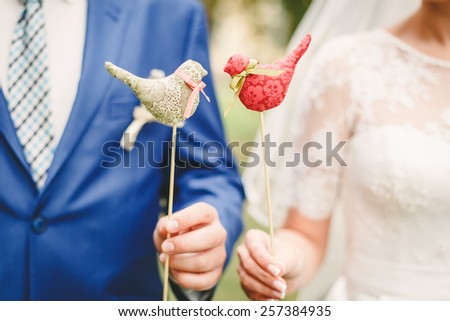 Bride and groom in bright clothes with wedding birds. sweet wedding details on the wedding day  - stock photo