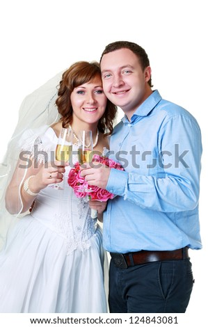 Bride and groom in studio with glasses of champagne in their wedding day - stock photo