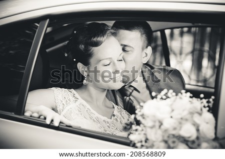 bride and groom in the car - stock photo