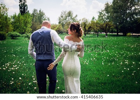 bride and groom in the park on nature. He hugs her shoulders. She touched his buttocks. - stock photo