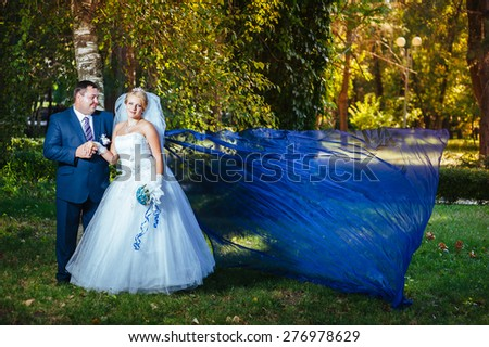 Bride and groom in the park with flying fabric - stock photo