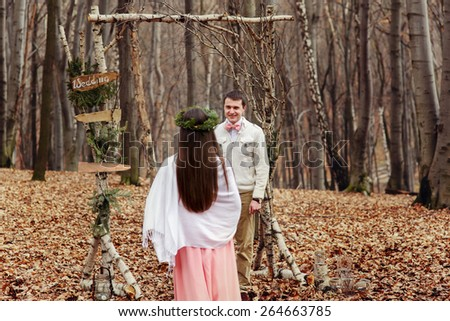 bride and groom in the wedding ceremony in forest near the decorate arch - stock photo