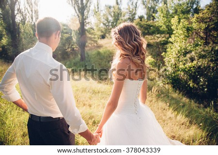 bride and groom is running with joined hands on a city park road sunshine - stock photo