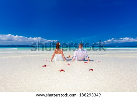 Bride and Groom jumping on tropical beach shore with red starfish in the sand - stock photo