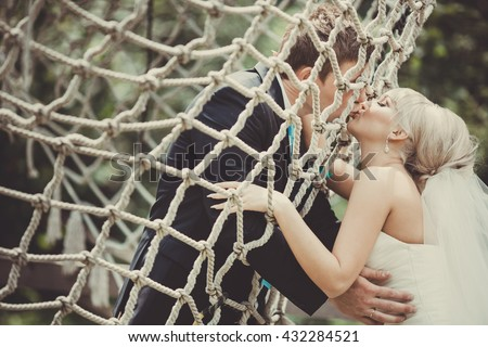 Bride and groom kiss hugging through the net
