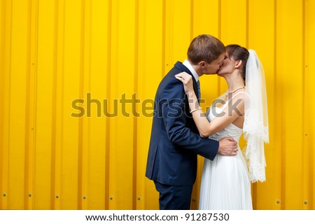 Bride and groom kissing against yellow wall - stock photo
