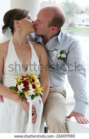 Bride and groom kissing during their wedding day ceremony.