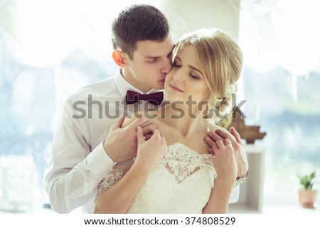 Bride and groom kissing in a church after wedding ceremony - stock photo