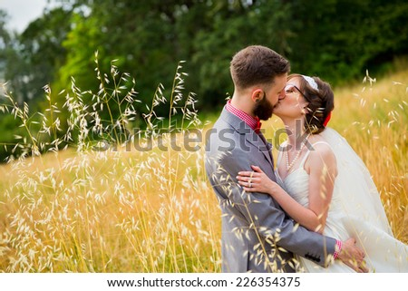 Bride and groom kissing in a field on their wedding day. - stock photo