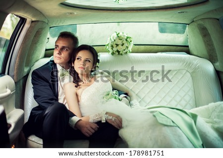 Bride and groom kissing in limousine on wedding-day. - stock photo