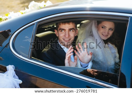 Bride and groom kissing in limousine on wedding-day - stock photo