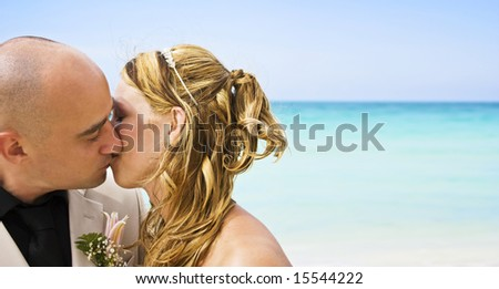 Bride and groom kissing on the beach - stock photo