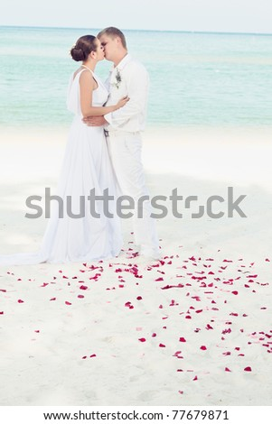 Bride and groom kissing on the tropical beach - stock photo