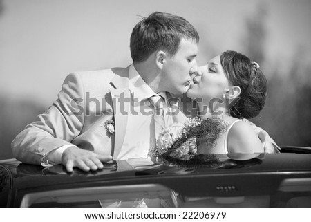 Bride and groom kissing on wedding auto