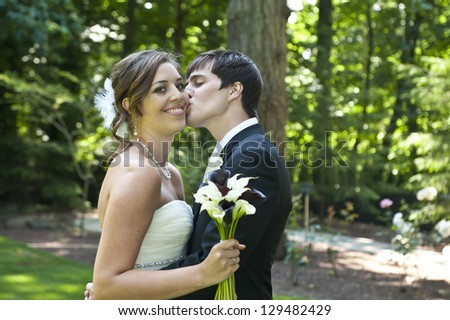 Bride and groom kissing on wedding day - stock photo