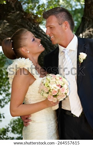 Bride and groom kissing on wedding-day outdoors. Side view. - stock photo