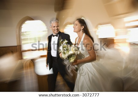 Bride and groom leaving church with motion blur effect. - stock photo