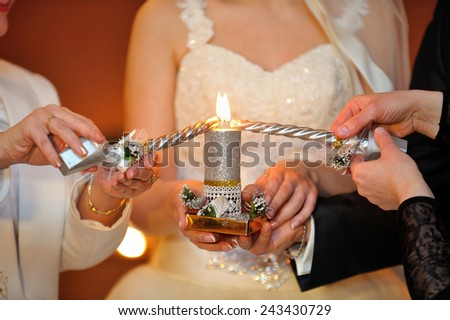 bride and groom lighting candle - stock photo