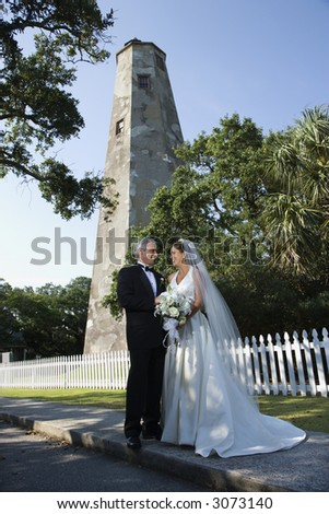 Bride and groom looking at each other with lighthouse in background. - stock photo