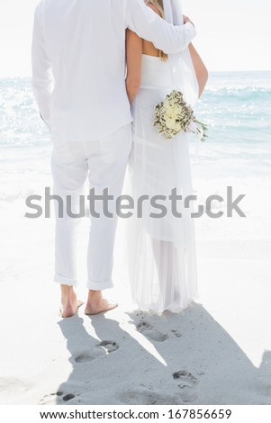 Bride and groom looking out to sea at the beach - stock photo