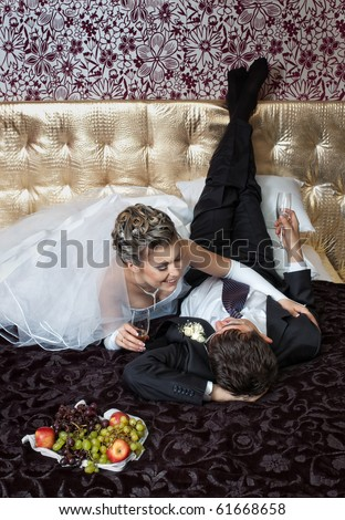 Bride and groom lying in a stylish bedroom with fruits and wineglasses - stock photo