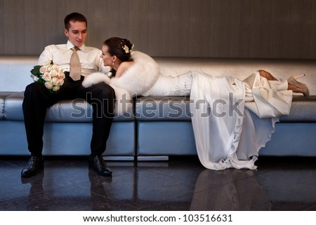 Bride and groom lying in a stylish lounge on  sofa