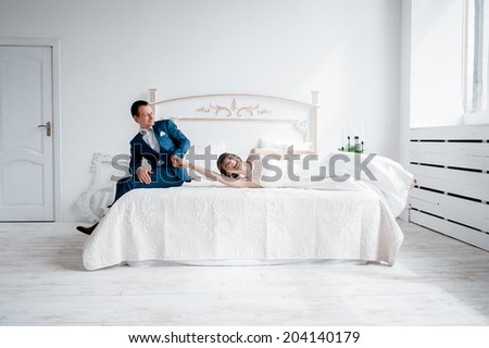 bride and groom lying on the bed. kiss and hug each other - stock photo
