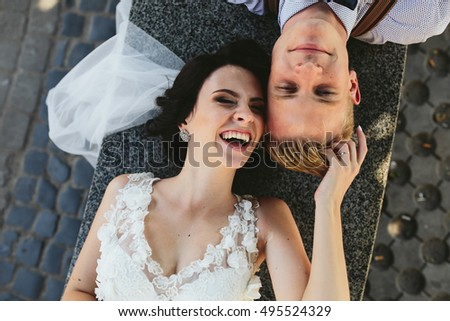 Bride and groom lying on the bench and having fun