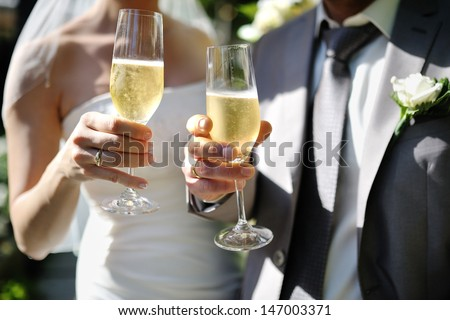 Bride and groom making a toast with champagne glasses after wedding ceremony - stock photo