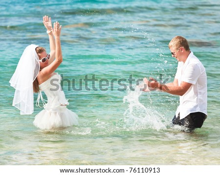 Bride and groom making splash in the sea - stock photo