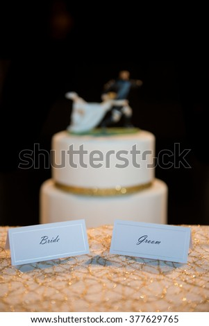 Bride and groom name card placeholders in front of layered wedding cake with rugby player and bride decoration on top - stock photo