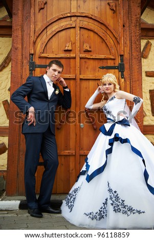Bride and groom near big wooden door - stock photo