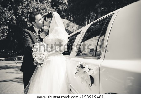 bride and groom near the limousine with wedding bouquet - stock photo