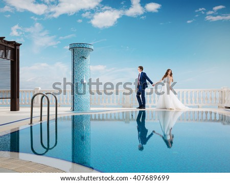 Bride and groom near the swimming pool. Honeymoon wedding the young couple. A man in a suit holding the hand of a woman in a beautiful dress. Luxury resort.