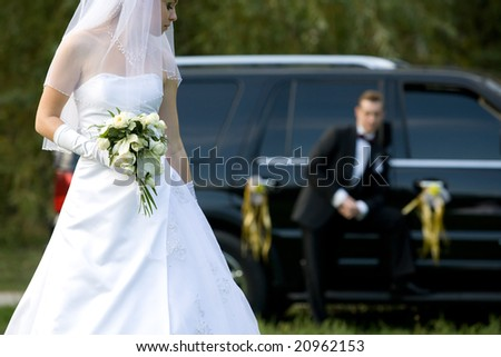 Bride and groom next to luxury wedding car - stock photo