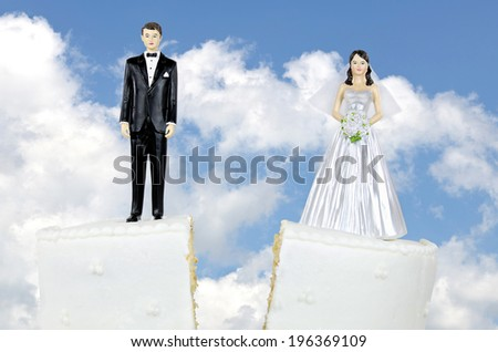 bride and groom on a split wedding cake tier - stock photo