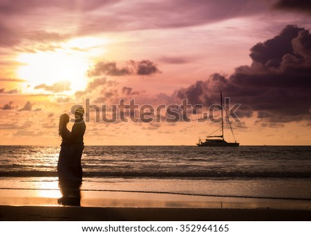 bride and groom on a tropical beach with the sunset - stock photo