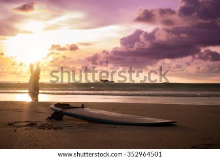 bride and groom on a tropical beach with the sunset and surf board - stock photo