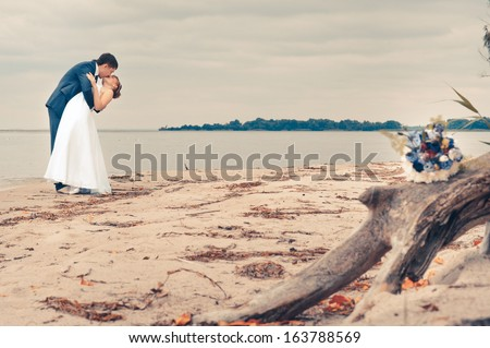 bride and groom on the beach, a wedding bouquet, wedding dresses - stock photo