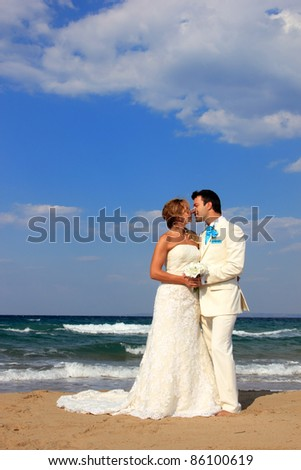 Bride and groom on the beach  on their wedding day
