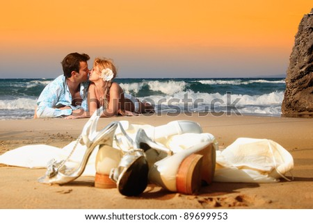 Bride and groom on the beach on their wedding day - stock photo