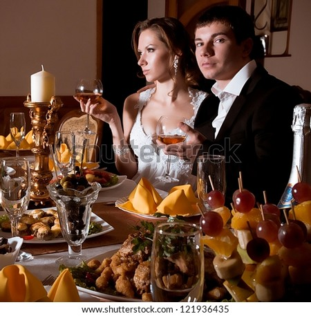 Bride and groom on their wedding day in a luxurious restaurant with banquet - stock photo