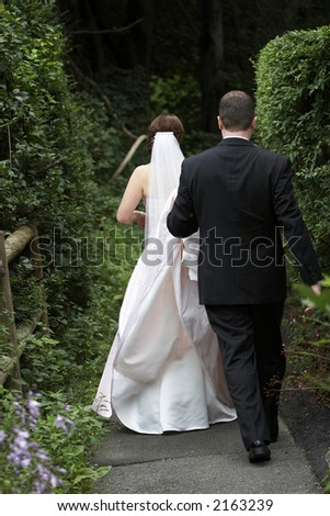 Bride and groom on their wedding day walking away from the camera down a path overgrown with trees