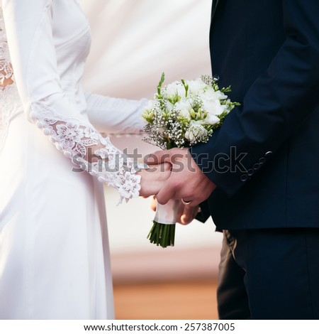 Bride and groom on wedding ceremony. Focused on wedding bouquet - stock photo