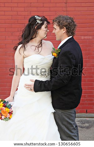 Bride and Groom on wedding Day - Red Brick wall as background